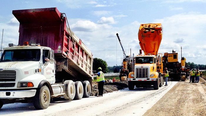 Several large trucks being used in construction