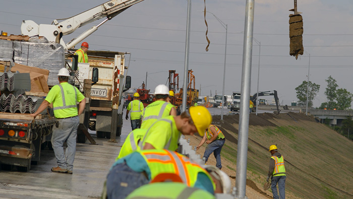 Group of craft laborers installing guardrails